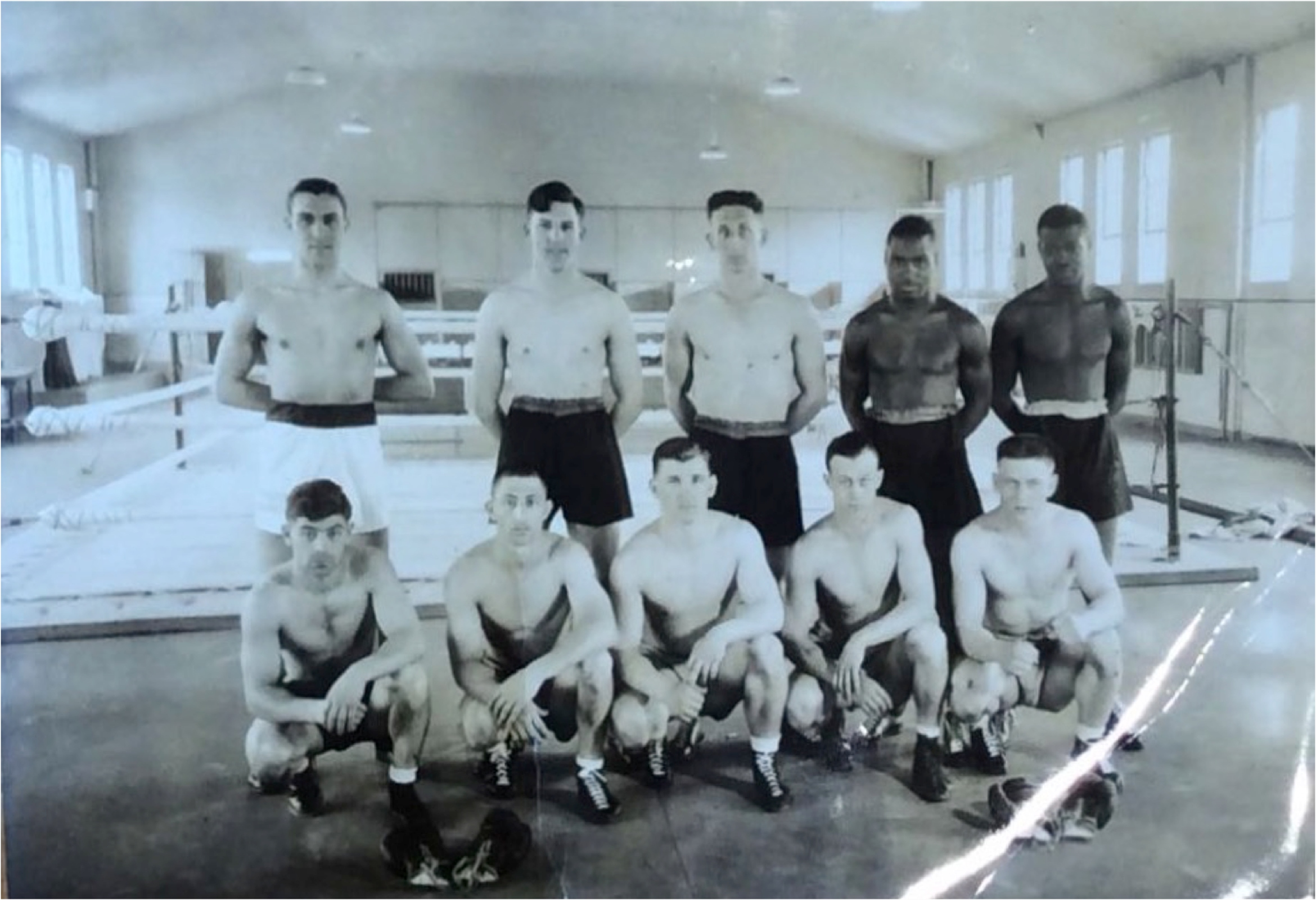 Ten incarcerated men who are members of a prison boxing team. Five men are standing with five kneeling in front of them. All of them are shirtless and wearing boxing shorts and shoes. In the background is a boxing ring. They are inside of a gym.