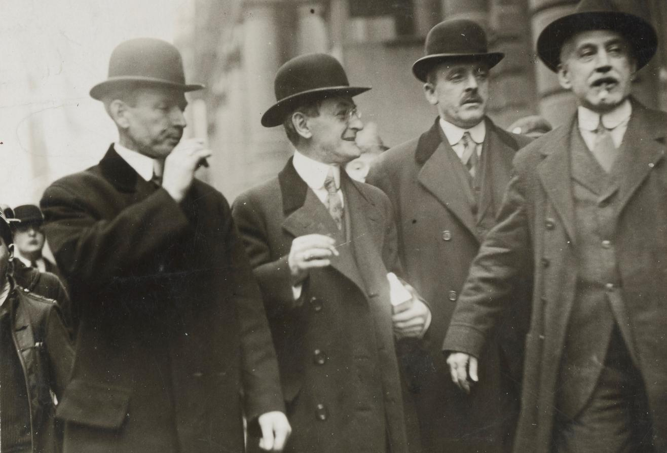 Photograph of three U.S. marshals escorting Carl Muck from the Federal Building in Boston in 1918.