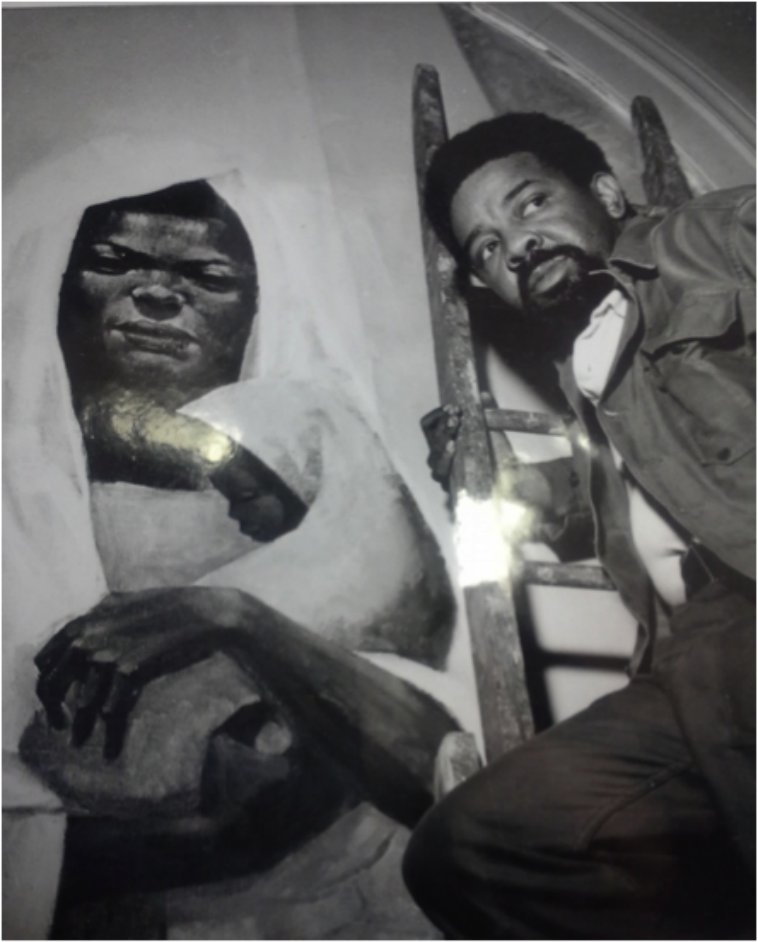 A photograph of a bearded African American man on a ladder next to a painting of Black Madonna.