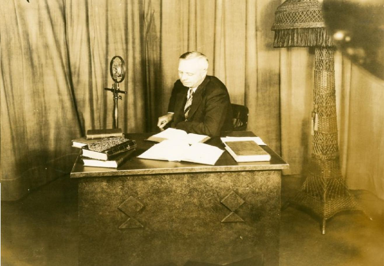 An image of Albert reading books while sitting at a desk.
