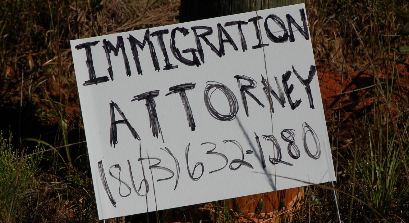 Photograph of a roadside sign advertising the telephone number of an immigration attorney.