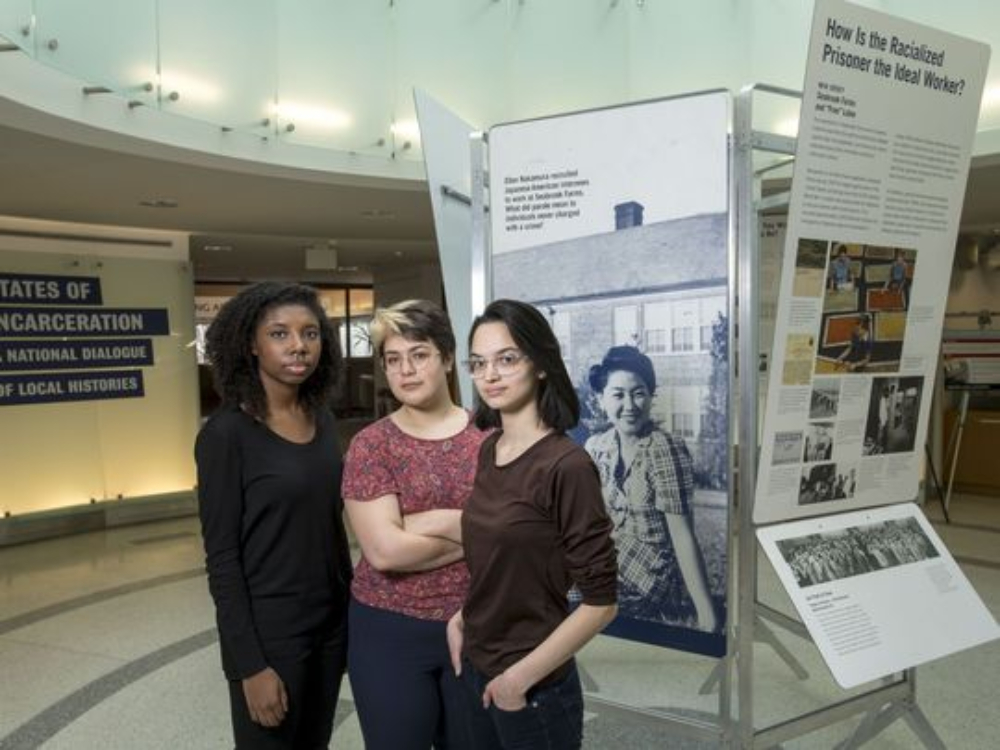 Three women standing in front of the States of Incarceration exhibit in the lobby of a public university library