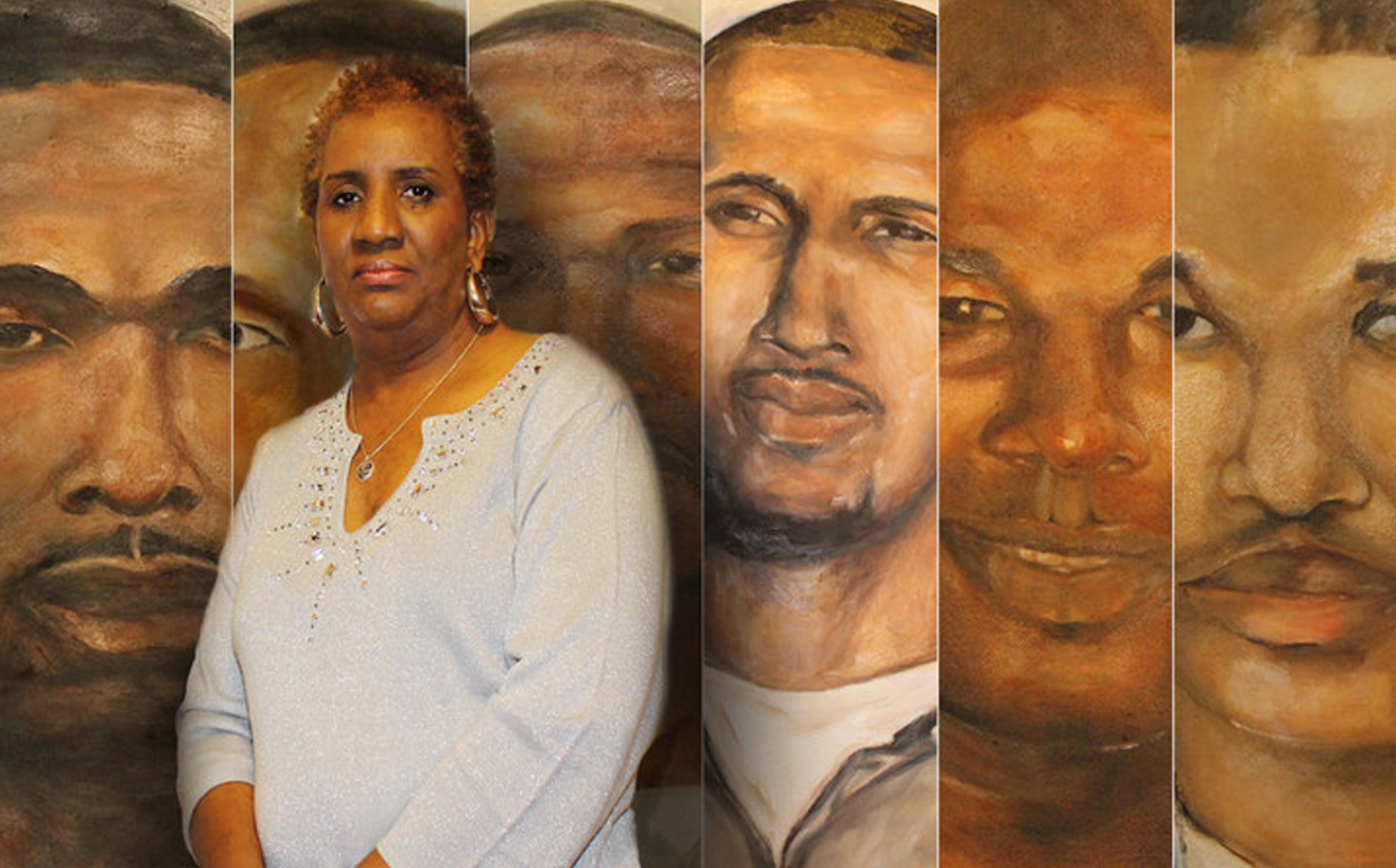 A black woman stands in front of a portrait of her son that she painted.