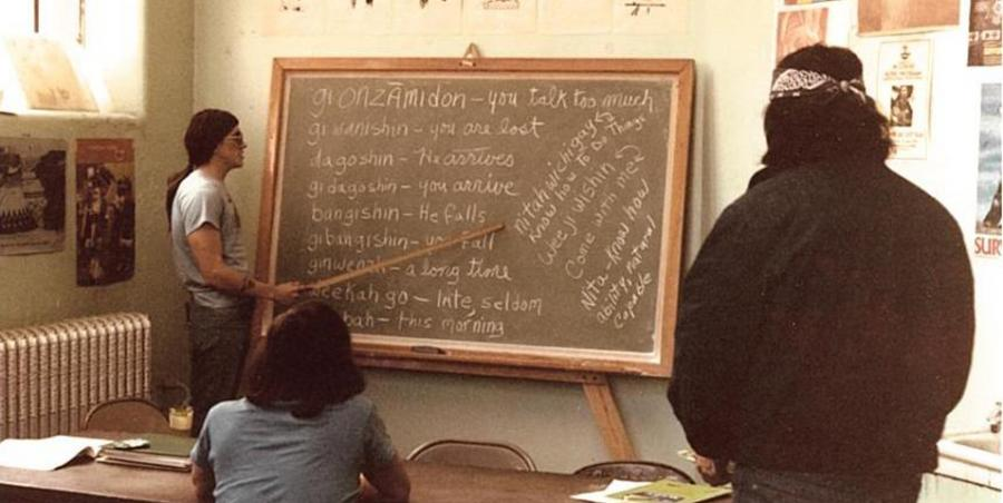 A historical photo showing a language class being taught as a part of the American Indian Movement. The photo shows the instructor pointing to a list of words and their translations on a chalk board.