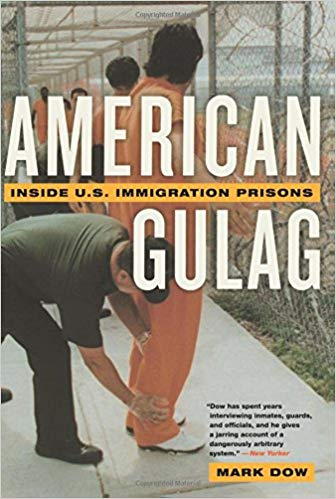 Cover of the book American Gulag by Mark Dow. The image shows a group of men in orange jumpsuits at an immigration detention facility. They are standing in front of a chain link fence and being patted down by uniformed officers.