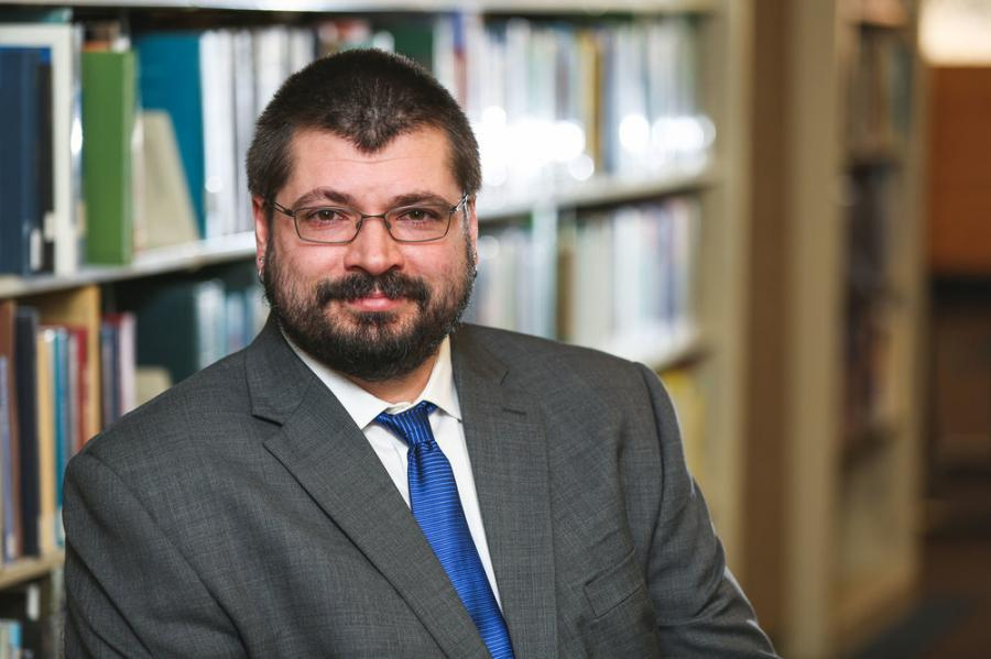 An image of Aaron T. Kinzel from the chest up in a grey suit jacket, white shirt, and blue tie. He is sitting in front of a library bookshelf.